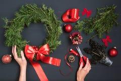 Mani del fiorista che fanno la corona di Natale Fotografia Stock