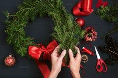 Mani del fiorista che fanno la corona di Natale Immagine Stock Libera da Diritti