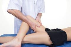 Mani del fisioterapista maschio che massaggiano la gamba della femmina Immagine Stock Libera da Diritti