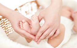Mani del genitore che mantengono i piedi del bambino appena nato immagine stock libera da diritti