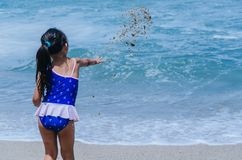 Mani del gioco della bambina con la sabbia immagine stock