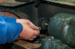Mani del gioielliere che lucida il pezzo in lavorazione dell'anello di oro Fotografie Stock Libere da Diritti
