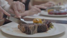 Mani del giovane nella priorità alta e della donna nella bistecca saporita di taglio del fondo che si trova sul piatto con le fog video d archivio
