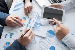 Mani del gruppo di affari al lavoro con il business plan e una compressa o immagine stock libera da diritti