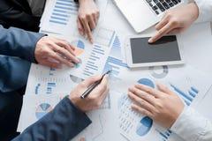 Mani del gruppo di affari al lavoro con il business plan e una compressa o fotografie stock libere da diritti
