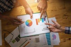 Mani del gruppo di affari al lavoro con il piano finanziario e su di legno Immagini Stock