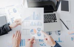 Mani del gruppo di affari al lavoro con il piano finanziario e una compressa, immagini stock
