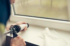 Mani del lavoratore che per mezzo di un tubo del silicone per la riparazione della finestra fotografia stock