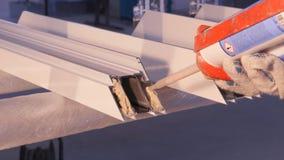 Mani del lavoratore che per mezzo di un tubo del silicone per la riparazione della finestra dell'interno Dettagli della finestra  Fotografie Stock Libere da Diritti