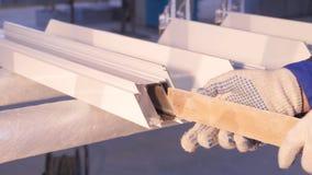 Mani del lavoratore che per mezzo di un tubo del silicone per la riparazione della finestra dell'interno Dettagli della finestra  Immagine Stock Libera da Diritti