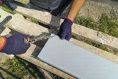 Mani del lavoratore in guanti protettivi che preparano il metallo di taglio del davanzale della finestra del PVC con il primo pia fotografie stock libere da diritti