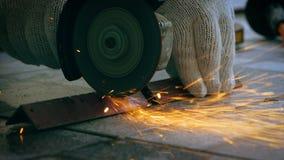 Mani del meccanico che usando smerigliatrice elettrica a tagliare l'acciaio con la luce intermittente della luce del fuoco video d archivio