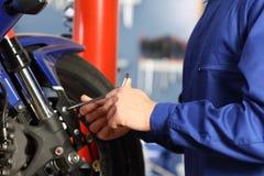 Mani del meccanico della motocicletta che smontano le parti Immagini Stock Libere da Diritti
