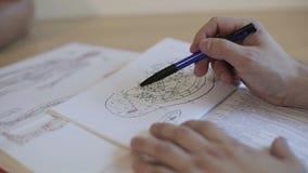 Mani del medico sul libro con un'illustrazione di un orecchio umano e dei punti di agopuntura video d archivio