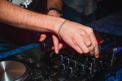 Mani del miscelatore del DJ per giocare la musica in night-club Fotografie Stock
