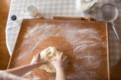 Mani del panettiere che impastano pasta Fotografie Stock