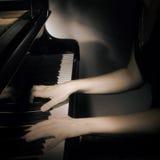 Mani del piano sullo strumento musicale Fotografia Stock
