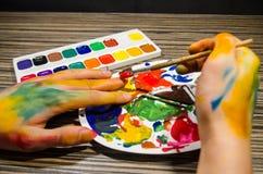 Mani del pittore che fanno un manicure con i colori rossi di gouache fotografia stock libera da diritti