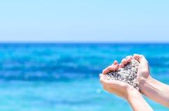 Mani del primo piano con la sabbia nella forma di cuore contro il mare tropicale del turchese Immagine Stock
