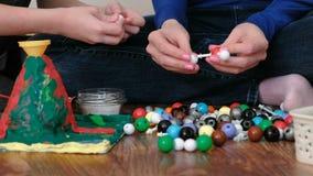 Mani del primo piano dei modelli della molecola della costruzione del figlio e della mamma dell'insieme di plastica colorato dell video d archivio
