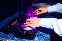 Mani del primo piano del DJ che giocano musica sul miscelatore del club Fotografie Stock Libere da Diritti