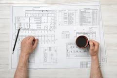 Mani del primo piano dell'uomo che tengono il caffè della tazza sopra la disposizione del disegno nella vista superiore Fotografia Stock Libera da Diritti