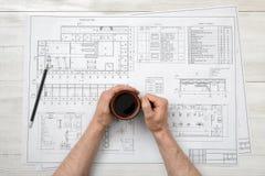 Mani del primo piano dell'uomo che tengono il caffè della tazza sopra la disposizione del disegno nella vista superiore Immagini Stock Libere da Diritti