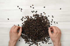 Mani del primo piano dell'uomo su una superficie di legno con i chicchi di caffè spanti Immagine Stock