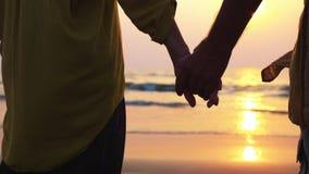 Mani del primo piano della condizione senior delle coppie sulla spiaggia e di ammirare un tramonto archivi video