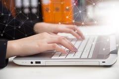 Mani del primo piano della donna di affari che funzionano e che scrivono sul computer portatile KE Fotografia Stock