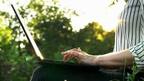 Mani del primo piano della donna di affari che scrivono sul computer portatile, computer di uso della donna al tramonto in parco video d archivio