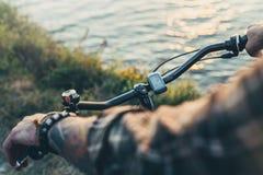 Mani del primo piano di giovane ciclista sui manubri, concetto di viaggio di attività di festa di vacanza del fuoco di selezione fotografie stock