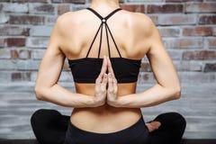 Mani del primo piano di yoga di pratica della giovane donna con namaste dietro il posteriore, sedentesi nell'esercizio di seiza,  Immagine Stock