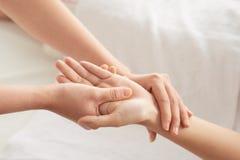 Mani del raccolto che massaggiano polso e palma immagine stock