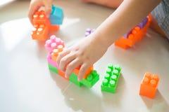 Mani del ragazzo che giocano con i blocchi di plastica variopinti Fotografie Stock Libere da Diritti