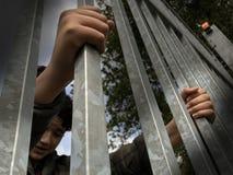 Mani del ragazzo dell'adolescente che tengono le forti sbarre di ferro Visto da sotto Crisi del rifugiato e dell'immigrato Recint immagine stock libera da diritti