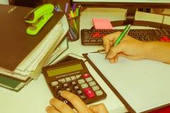 Mani del ragioniere con il calcolatore e la penna Fotografia Stock