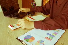 Mani del ragioniere con il calcolatore e la penna Fondo di contabilità Fotografia Stock