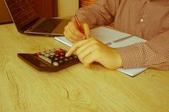 Mani del ragioniere con il calcolatore e la penna Fondo di contabilità Immagini Stock Libere da Diritti