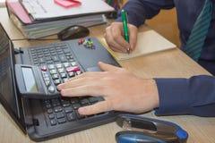 Mani del ragioniere con il calcolatore e la penna Fondo di contabilità Uomo d'affari facendo uso di un calcolatore per calcolare  Fotografie Stock Libere da Diritti