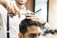 Mani del ` s del barbiere facendo uso delle forbici per tagliare i capelli del ` s del cliente immagini stock libere da diritti