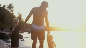 Mani del ` s dei bambini della tenuta del papà al bello tramonto e camminare sulla spiaggia tropicale Concetto di festa di viaggi immagini stock
