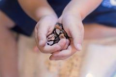 Mani del ` s dei bambini del primo piano con i piccoli oggetti immagine stock libera da diritti