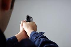 Mani del ` s dell'ufficiale di polizia che tendono con la pistola Immagini Stock