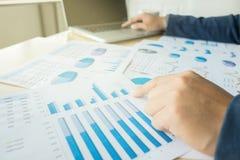 Mani del ` s dell'uomo di affari al lavoro con il piano finanziario e un computer portatile immagine stock