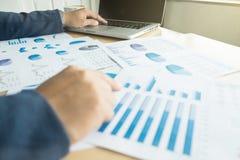 Mani del ` s dell'uomo di affari al lavoro con il piano finanziario e un computer portatile immagini stock