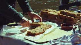 Mani del ` s della donna che affettano dolce alla stalla B del forno del mercato Fotografia Stock