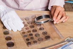 Mani del ` s della donna con la lente d'ingrandimento e una collezione di monete Immagini Stock