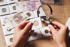 Mani del ` s della donna con la lente d'ingrandimento e una moneta Fotografia Stock Libera da Diritti