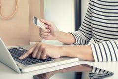 Mani del ` s della donna facendo uso del registro della carta di credito e dello sho online di pagamenti Immagini Stock